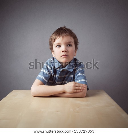 Little boy sitting at desk on grange background - stock photo