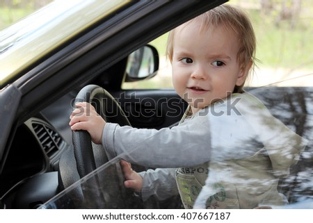 Little boy sitting behind the wheel of a car with a lovely smile on his face, outdoors, family travel concept - stock photo