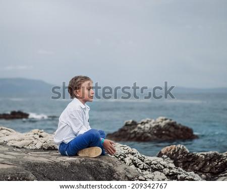 Little boy sitting calm on the solitade sea beach - stock photo