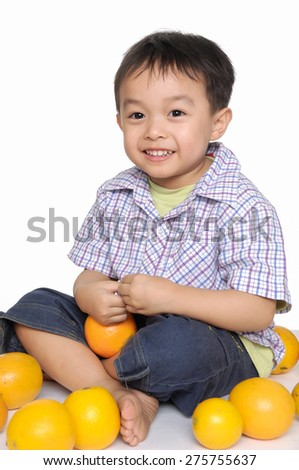 little boy sitting floor with pile of oranges - stock photo