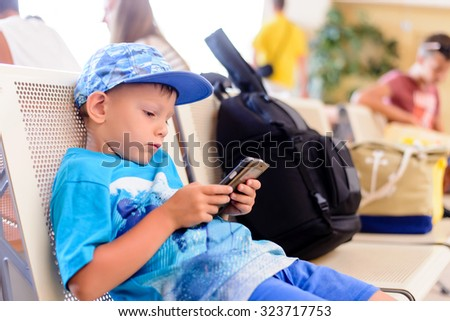 Little boy sitting in an airport departure hall contentedly playing on his tablet or mobile phone as he waits for his flight with his luggage - stock photo