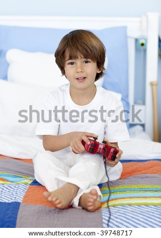 Little boy sitting in bed playing videogames - stock photo