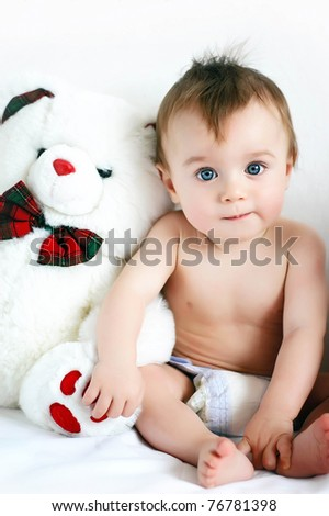 Little boy sitting next to a teddy bear - stock photo