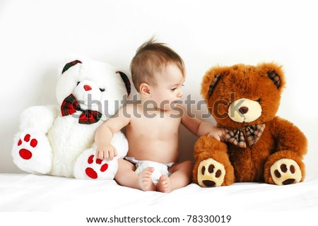 Little boy sitting next to a teddy bears - stock photo