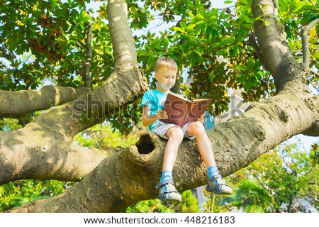 Little boy sitting on  big tree and reading book. - stock photo