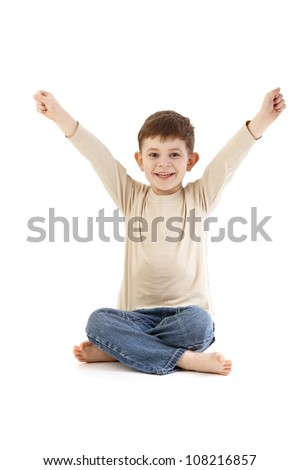 Little boy sitting on floor in tailor seat, smiling happily. - stock photo