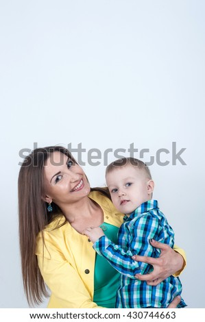 Little boy sitting on my mom's lap and clung to her breast - stock photo