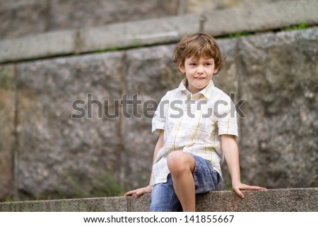 Little boy sitting on stone stairs - stock photo
