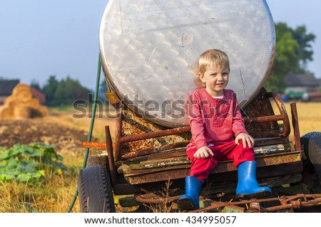 Little boy sitting on the agricultural machine / Portrait of a little blond boy in the field - stock photo