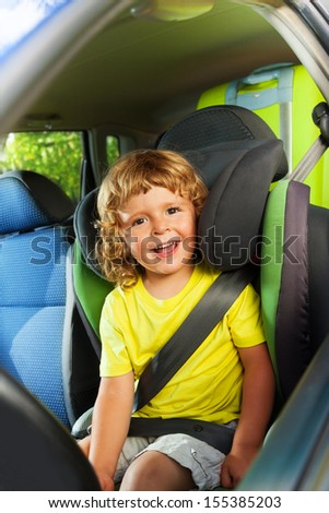 Little boy sitting on the child seat, happy and laughing on the back of the car - stock photo