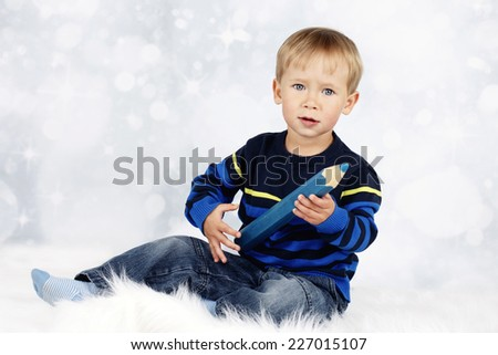 Little boy sitting on the floor with big crayon - stock photo