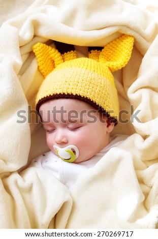 little boy sleeping on soft cream blanket - stock photo