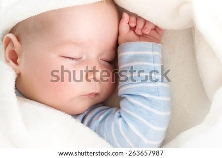 little boy sleeping on soft white blanket - stock photo