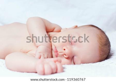 Little boy sleeping on white blanket - stock photo