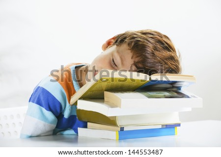 Little boy sleeping over books./ Tired schoolboy studying in home. - stock photo