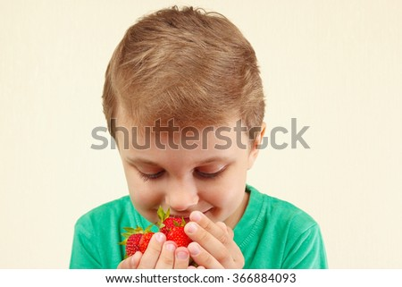 Little boy smelling a handful of sweet red strawberries - stock photo