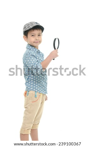 Little boy smiling and holding magnifier on a white background - stock photo
