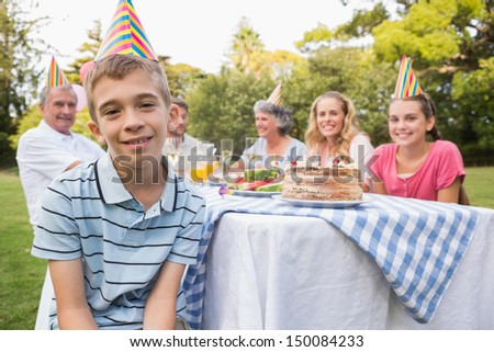 Little boy smiling at camera at his birthday party outside at picnic table - stock photo