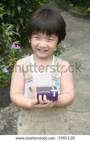 Little boy smiling happily and holding purple gift box - stock photo