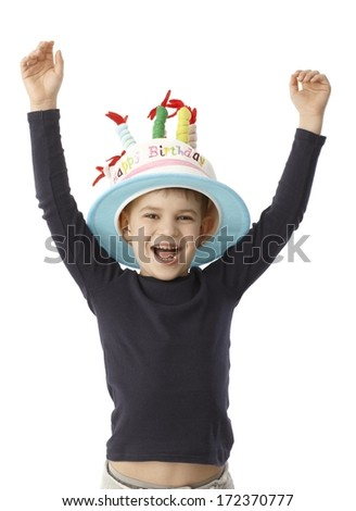 Little boy smiling happy on his birthday, wearing birthday cake hat with candles. - stock photo