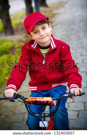 Little boy smiling on bike in park - stock photo