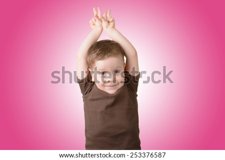little boy smiling with arms raised on a pink background - stock photo