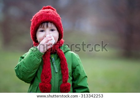Little boy, sneezing and blowing his nose outdoor on a sunny winter day - stock photo