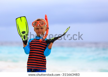little boy snorkeling with flippers at tropical beach - stock photo