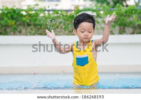 Little boy splashing in swimming pool - stock photo