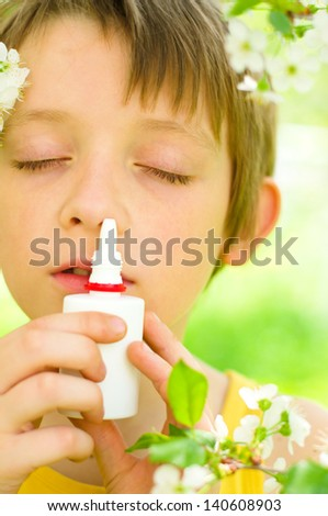 little boy spraying his nose outdoors - stock photo