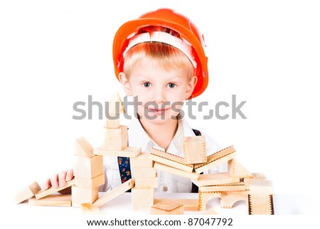 little boy stacks house from wooden blocks isolated on white background - stock photo