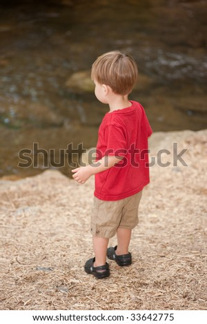 little boy standing by a creek - stock photo