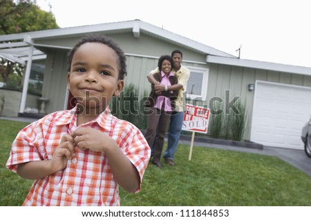 Little boy standing with his parents embracing in front of the house - stock photo