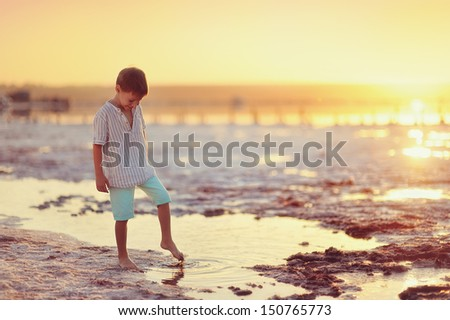 little boy stands barefoot at sunset on the sea - stock photo