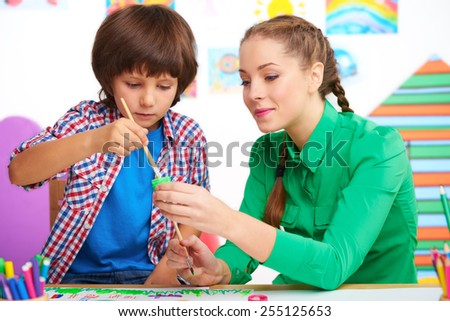 Little boy studying with young teacher in a preschool center for children. Teacher helping boy to draw some picture with paint - stock photo