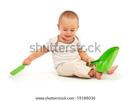 Little boy sweeping with green brush and holding the dust pan - stock photo