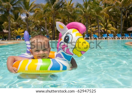 Little boy swimming with colorful floating toy - stock photo