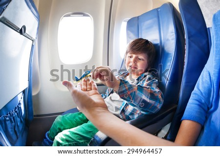 Little boy takes little plane from moms hand sitting by the window in jet airplane  - stock photo