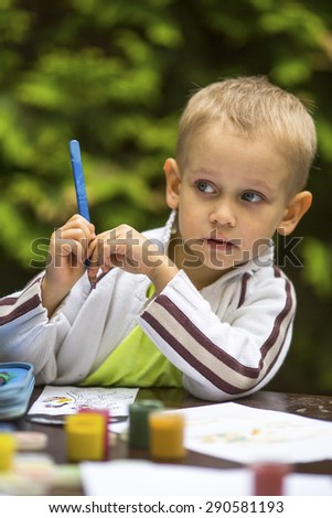 Little boy thinking with a pencil while drawing. - stock photo