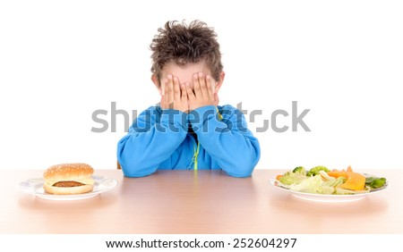 little boy torn between hamburguer and vegetables isolated in white background - stock photo