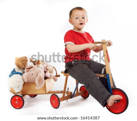 Little boy transporting his teddy bears and dolls in a cart - stock photo