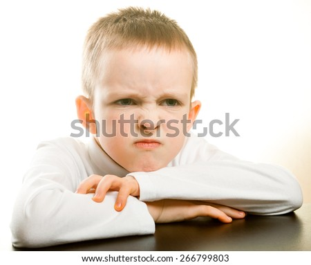 little boy upset about something on a white background - stock photo