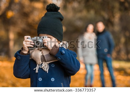Little boy uses an old camera while walking in autumn park with her parents - stock photo