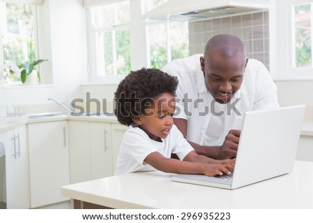 Little boy using a laptop with his father at home - stock photo
