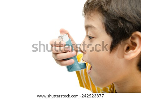 Little boy using Asthma inhaler for breathing on white background - stock photo