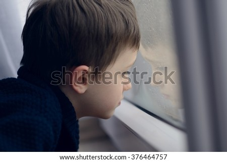 Little boy waiting by window for stop raining. Loneliness and waiting concept. Rainy day  - stock photo