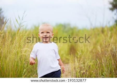 Little boy walking in a field - stock photo