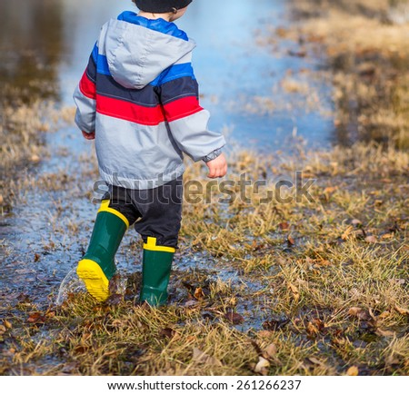 Little boy walking through puddles in the grass wearing rain boots. - stock photo