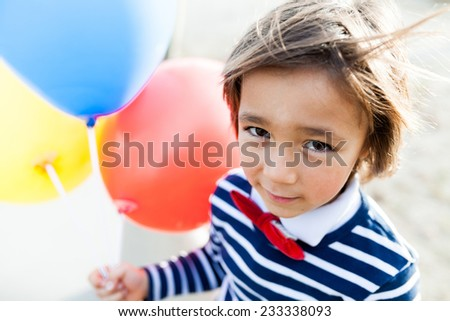little boy walking with balloons - stock photo
