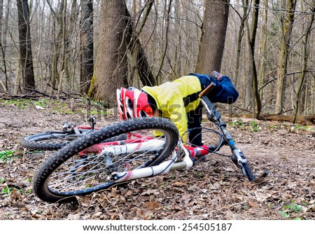 Little boy wearing a helmet raises big bike on the background of a spring forest - stock photo